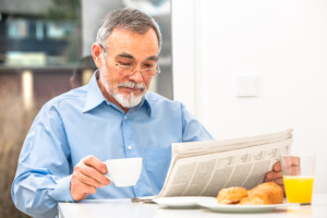 senior having tea while reading a newspaper