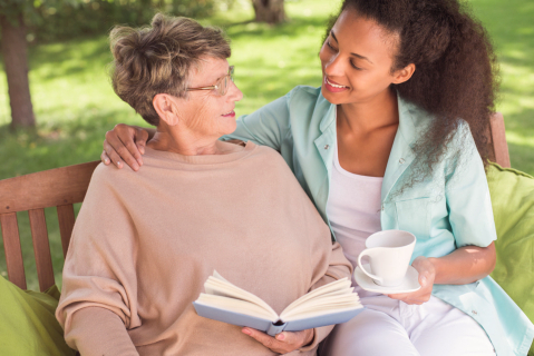 senior woman hold the book while the nurse is holding a cup